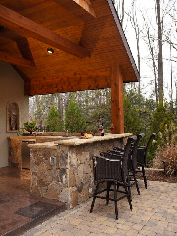 A Beautiful Covered Outdoor Kitchen Features A Bar With Stylish Woven Bar  Stools.